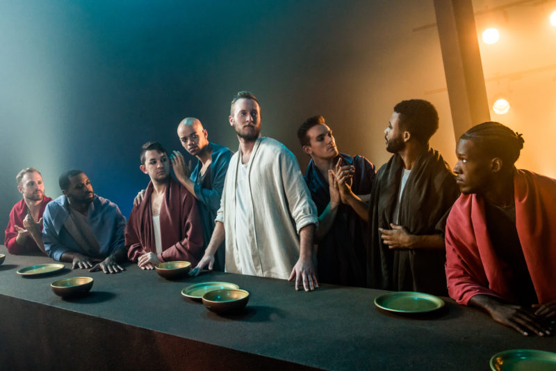 Jesus and his disciples stand behind one long table, posing in the same position as DaVinci's Last Supper
