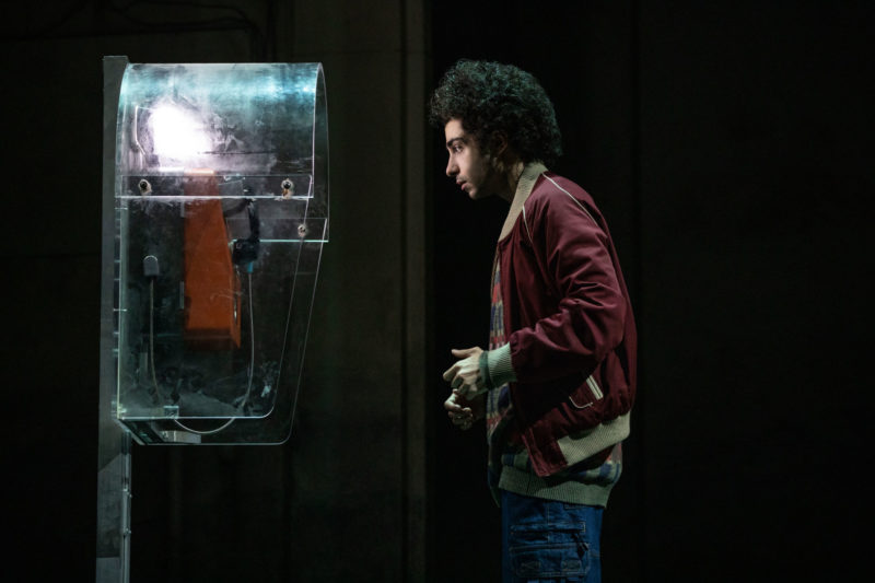 A young man waits anxiously at a pay phone for a phone call from his long distance girlfriend in a scene from THE BAND'S VISIT.